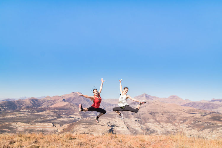 Happy Friends With Arms Raised Jumping On Mountain Against Clear Sky