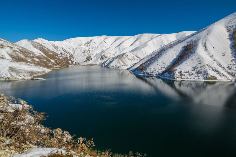 Beautiful mountain lake in winter. scenic view of snowcapped mountains and lake against blue sky.