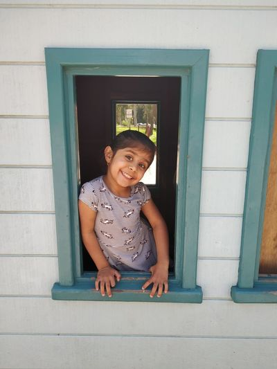 Portrait of smiling girl looking through window