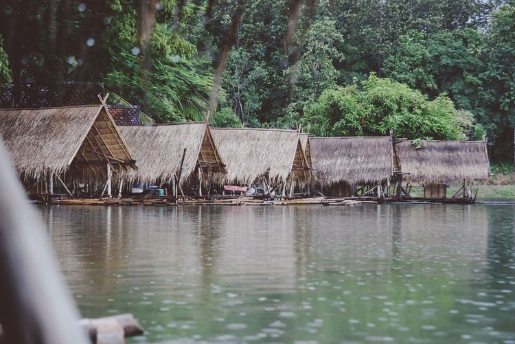 Wooden rafts with roofs moored in lake against trees