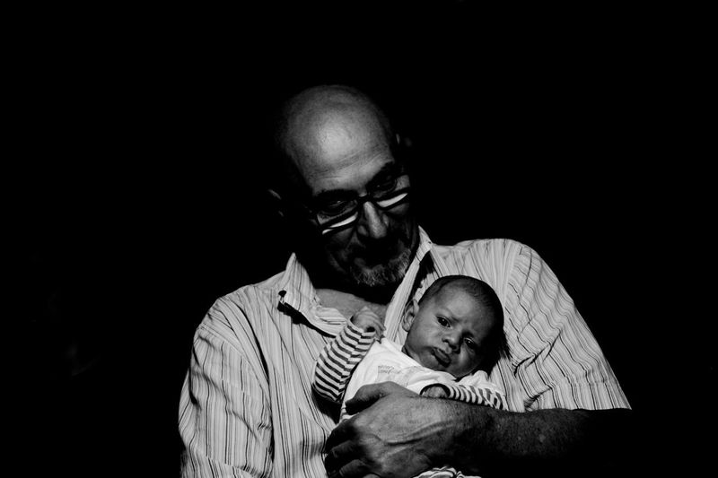 Grandfather And Grandchild Sitting Against Black Background