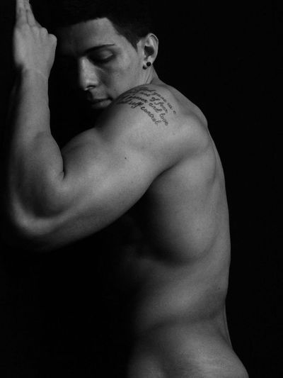 Side view of naked muscular man exercising against black background