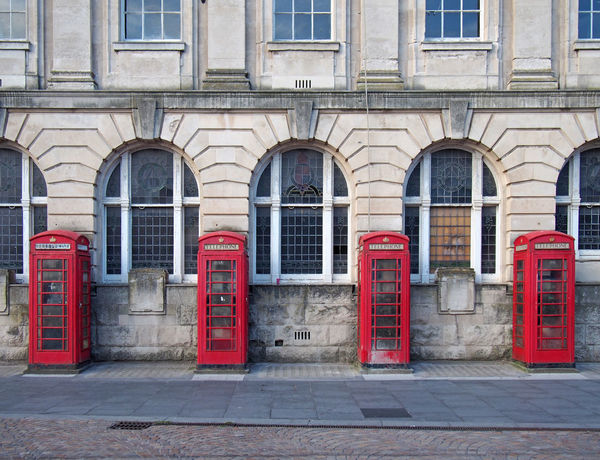 a line of four traditional british red phone boxes outside an old post office building in blackpool england Red Telephone Box Arch Architecture Building Building Exterior Built Structure City Day Door Entrance Façade Footpath In A Row No People Outdoors Red Sidewalk Street Telephone Booth The Past Window