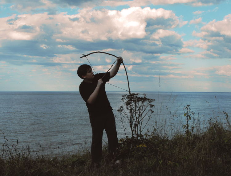 A boy shooting an arrow from a handmade bow by the sea with some dramatic clouds on background. Arrow Attempt Beach Bow And Arrow Boy Brave Child Childhood Cloud - Sky Clouds Day Horizon Over Water Kid Naive One Man Only One Person Only Men Outdoors People Sea Shooting Sky Standing Water Young Adult Uniqueness