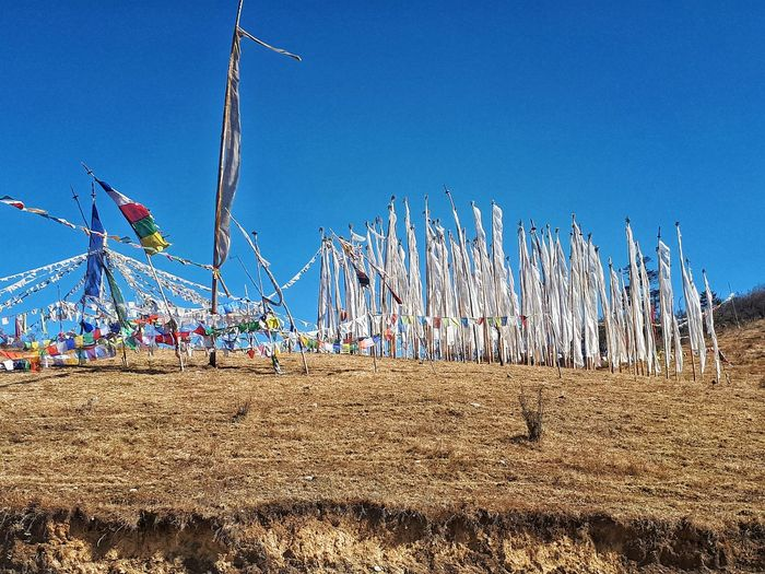 Panoramic shot of sailboats on field against clear blue sky