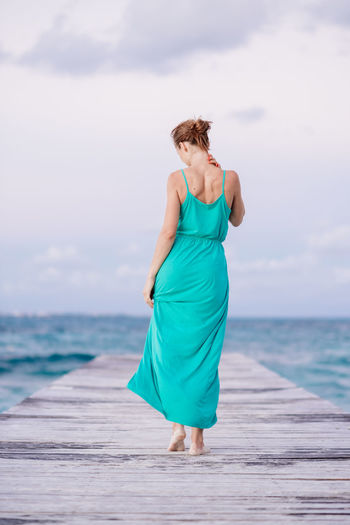 Walking away Lifestyle Beach Beauty In Nature Day Dock Full Length Horizon Over Water Leisure Activity Lifestyles Nature One Person Outdoors People Real People Sea Standing Water Young Adult Young Women
