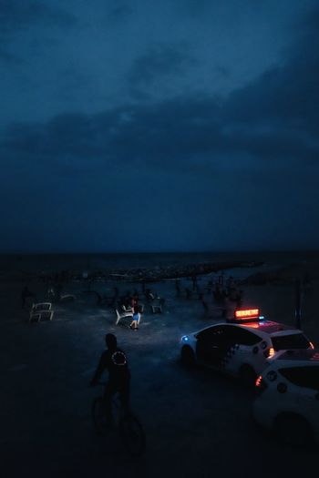 People on beach against sky at night