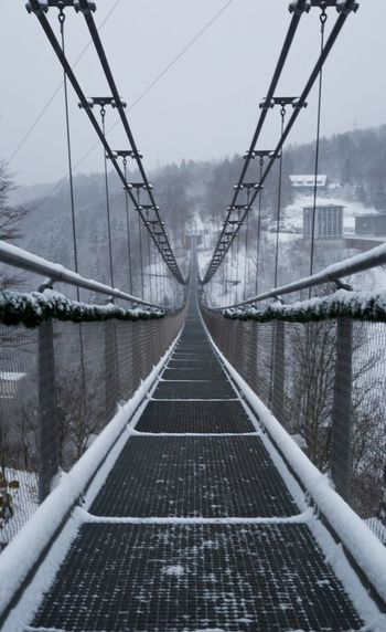 View of suspension bridge leading towards mountains during winter