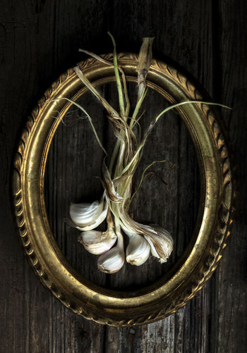 Directly above shot of garlic with gold frame on table