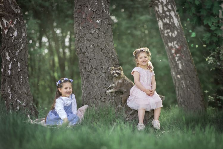 Girls sitting by sister and raccoon at forest