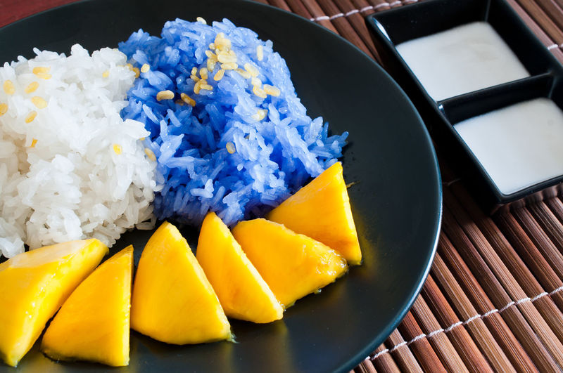 High Angle View Of White And Blue Rice With Mango Served In Plate On Place Mat