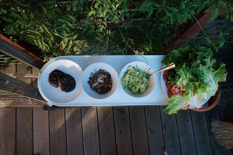Burger time, salad, mushrooms, guacamole Food And Drink Wood - Material Food Plant Table No People Day Healthy Eating High Angle View Freshness Directly Above Nature Wellbeing Ready-to-eat Outdoors Green Color Bowl Sunlight Plate