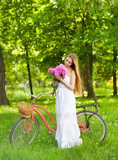 Woman with bicycle holding flower in park