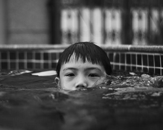 Portrait of cute boy swimming in pool