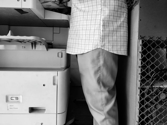 Midsection of man standing by photocopier