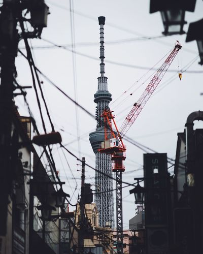 Low angle view of cranes against buildings in city