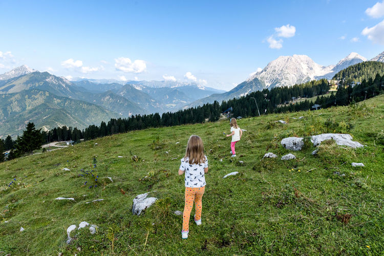Rear view of girls standing on field against mountains