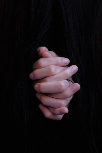Close-up of woman hand over black background
