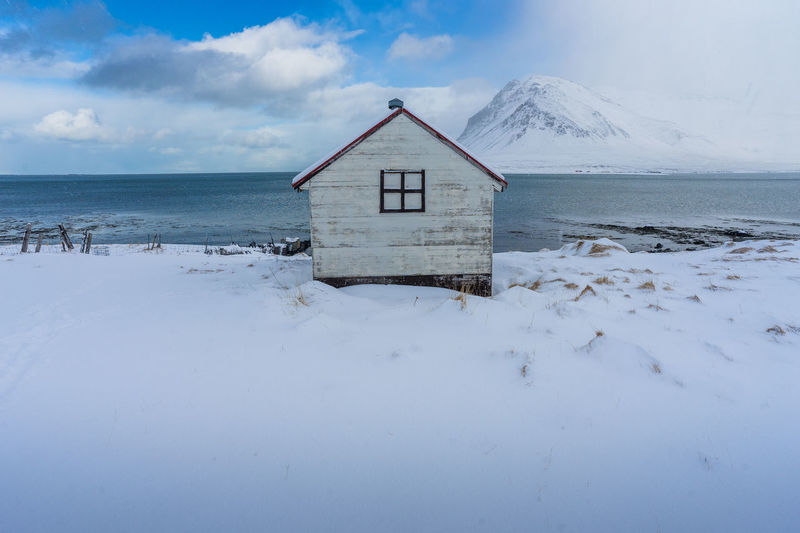 House by sea against sky during winter