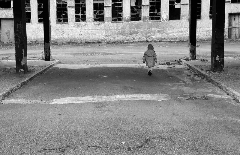 AntiM Black And White Friday Challenge Architecture Building Exterior Built Structure City Day Full Length One Child Only One Person Outdoors People Real People Road Sad Childhood Single Child Solitude Solitude And Silence Warm Clothing The Photojournalist - 2018 EyeEm Awards The Street Photographer - 2018 EyeEm Awards