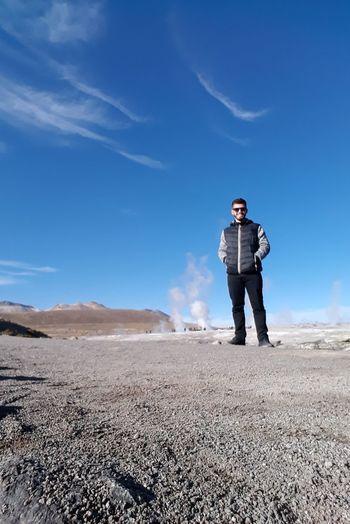 Full length of man standing on field against blue sky
