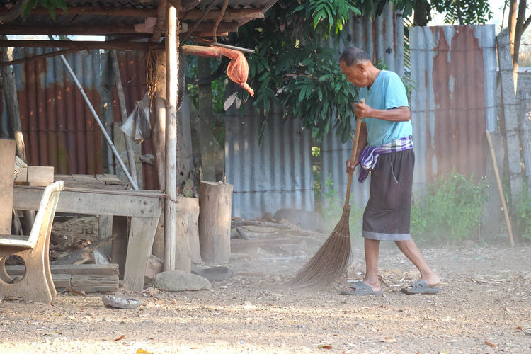 Side view of senior man sweeping land