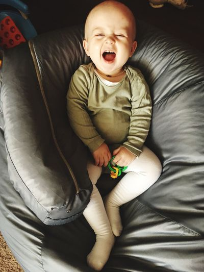 High Angle View Of Laughing Cute Baby Boy Sitting On Bean Bag At Home