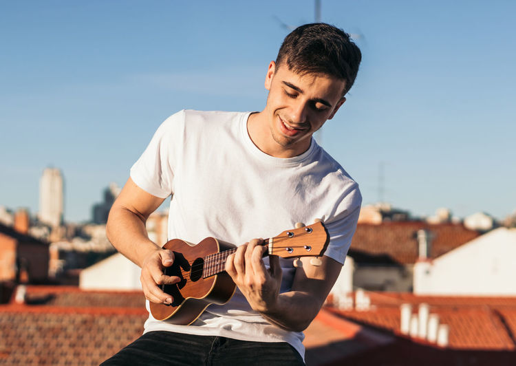 Young man playing guitar against sky