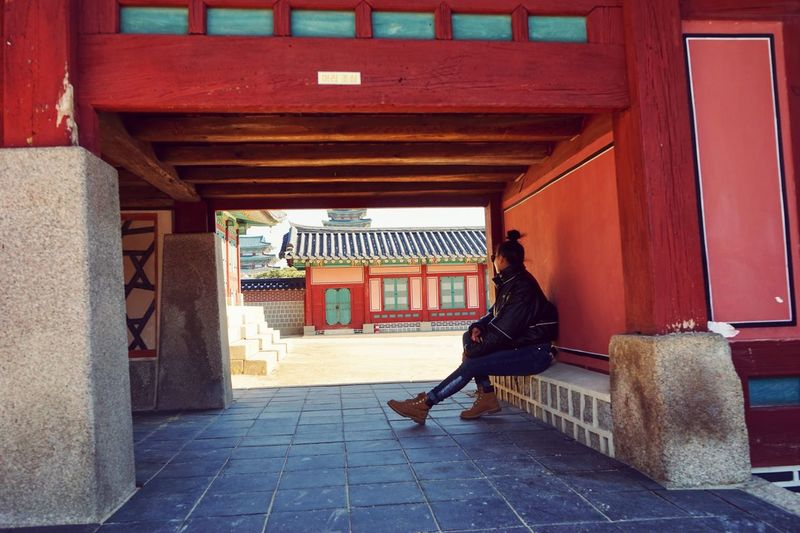 Full length of woman sitting in traditional building