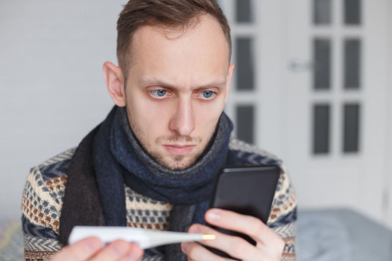 Man using mobile phone while holding thermometer