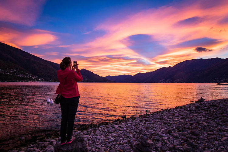 photographing a sunset in ticino Beauty In Nature Cloud - Sky Day Full Length Lago Maggiore Lake Leisure Activity Lifestyles Mountain Nature One Person Outdoors People Photographing Real People Scenics Sky Standing Sunset Switzerland Ticino Tranquil Scene Tranquility Water Be. Ready.