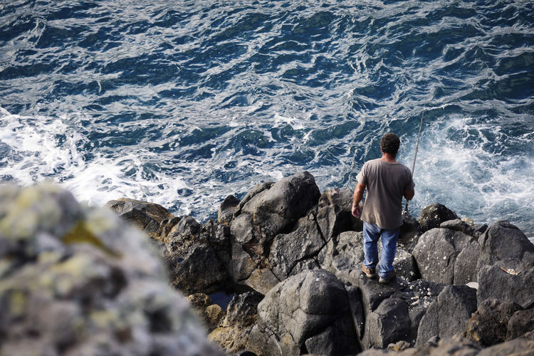 Rear View Of Man Standing On Rock At Sea