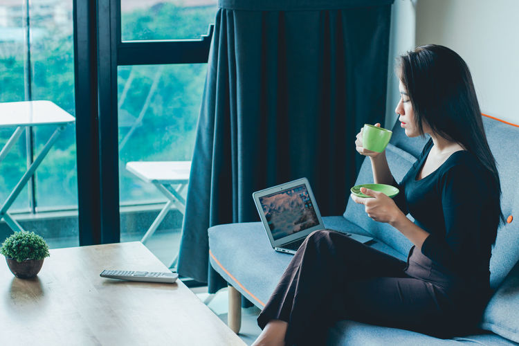 Woman having a cup of coffee while sitting on a sofa beside a laptop.