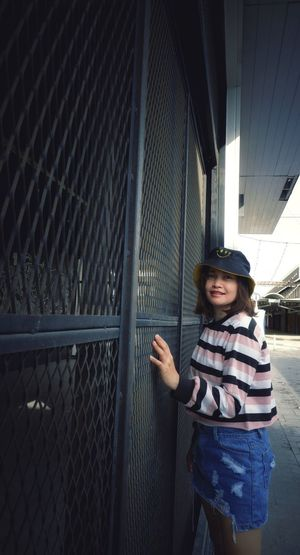 Portrait of smiling girl standing by fence