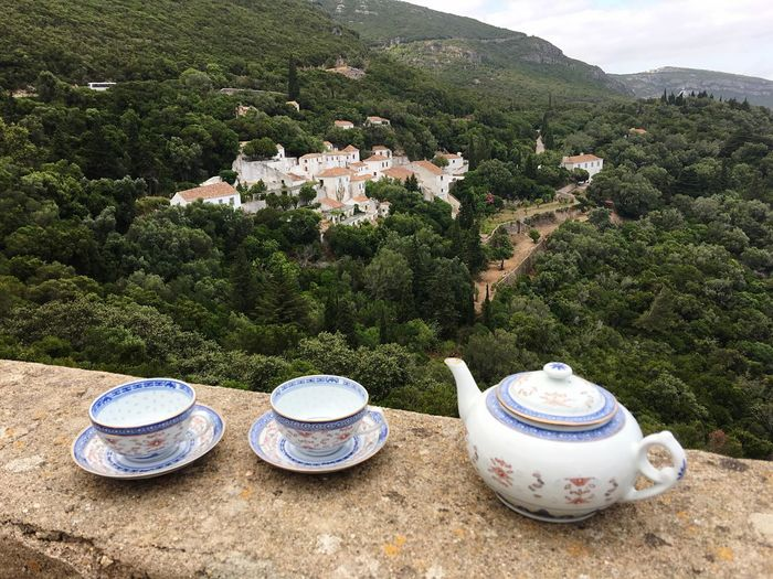 High angle view of kettle with tea cups and saucers on retaining wall