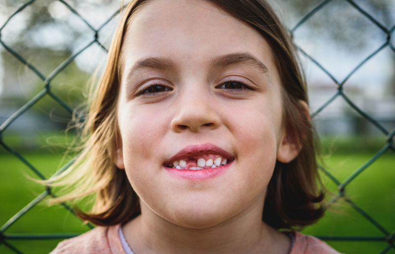 Close-up portrait of smiling girl against fence