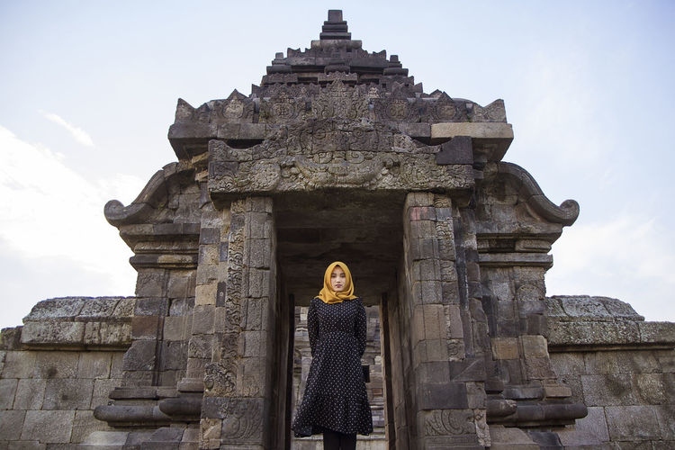 Muslim tourist woman wearing headscarf or hijab at plaosan temple, klaten, central java, indonesia