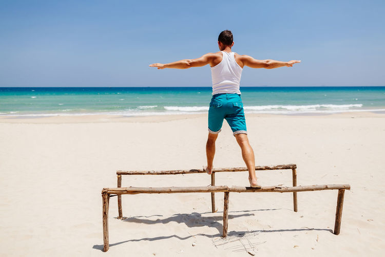 Man With Arms Outstretched Balancing On Wooden Structure At Beach During Sunny Day