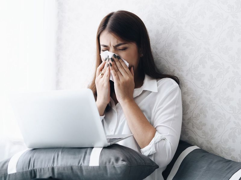 Asian young woman feeling unwell. Adult Bed Business Communication Computer Holding Home Interior Human Hand Indoors  Internet Laptop Lifestyles Occupation One Person Real People Sick Sitting Sneeze Sofa Technology Unwell Using Laptop Wireless Technology Working Young Adult