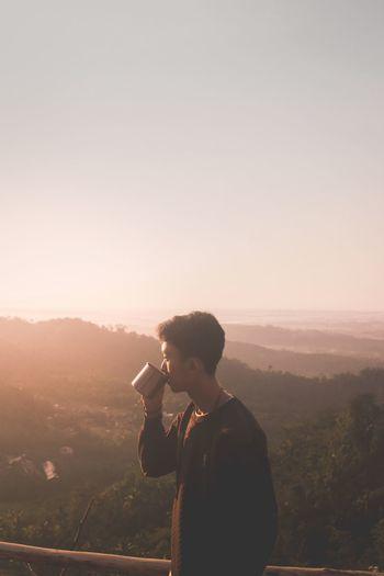 Side view of teenage boy drinking coffee on mountain peak against clear sky