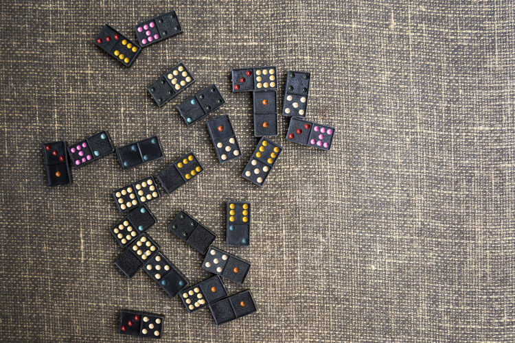 domino game,Colorful dominoes are arranged,Fabric background. Continuity Domino Fun Gambling Action Collection Concept Effect Enjoyment Entertainment Filling Game Group Leisure Number Pattern Pieces Play Row Sequence Strategy Symbol Table Tiles Toy