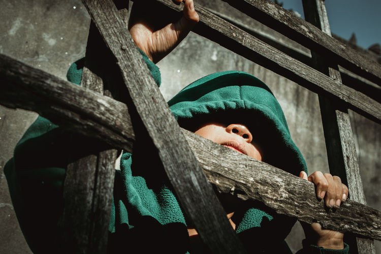 Low angle portrait of boy in hood standing at railing