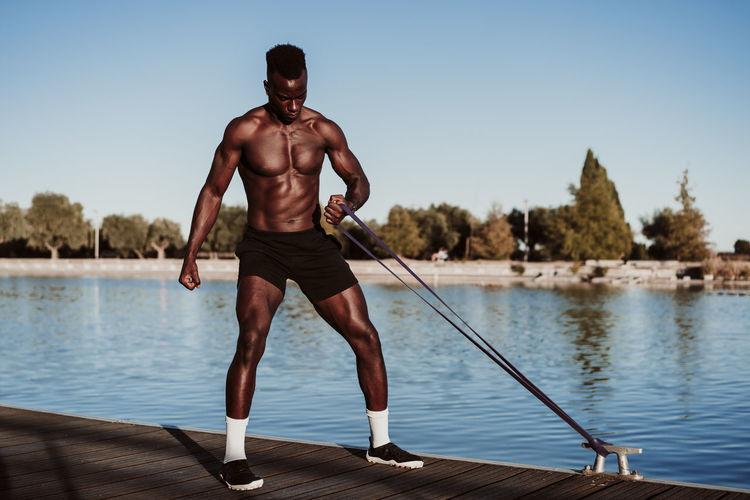 Full length of shirtless man in lake against sky