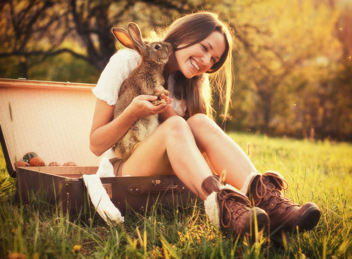 Young Woman With Rabbit Sitting On Field