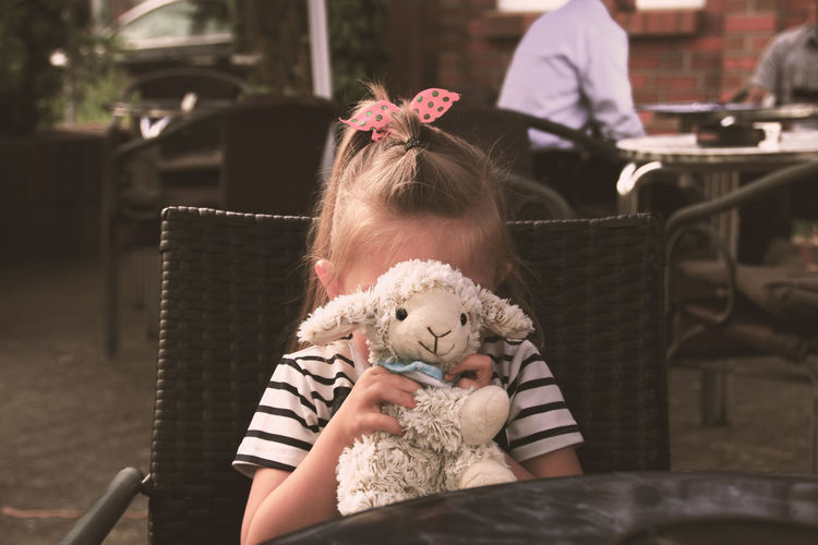 Girl Covering Face With Toy While Sitting At Cafe