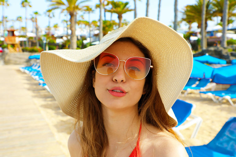 Portrait of young woman wearing sunglasses and hat at beach
