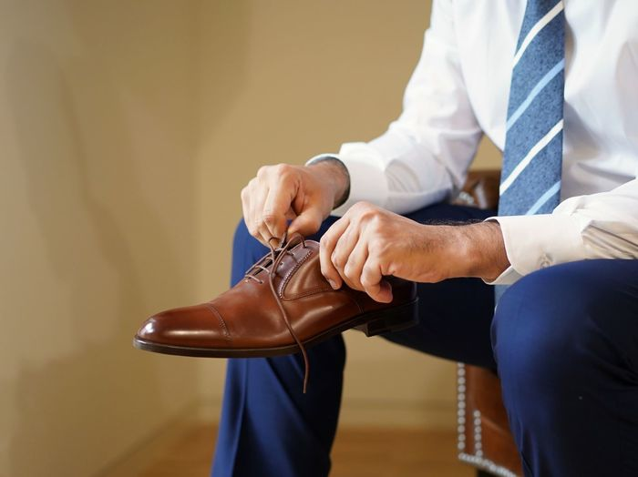 Midsection of businessman holding shoe sitting at home