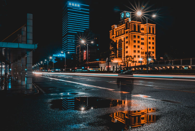 alone Illuminated City Architecture Night Street Building Exterior Road Transportation Built Structure Motion Long Exposure Sign City Street Street Light Mode Of Transportation Light Trail Sky Speed Symbol Blurred Motion No People Outdoors Light Office Building Exterior