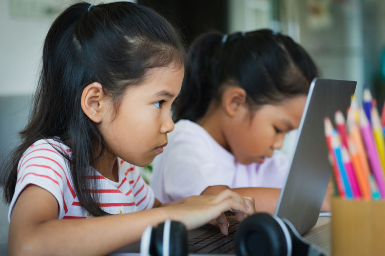 Women looking at camera while sitting in laptop