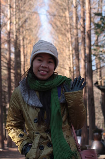 Portrait Of Smiling Woman Standing In Forest During Winter